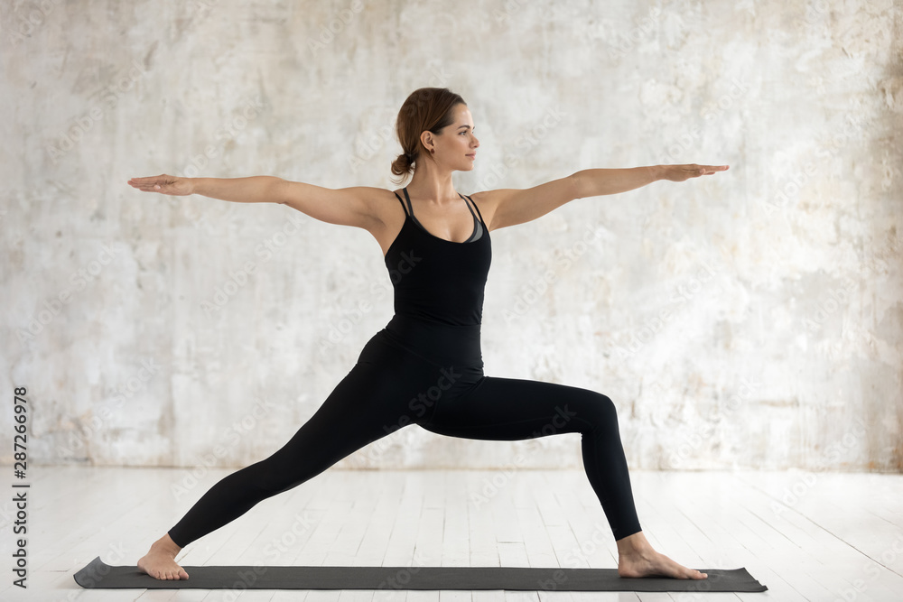 Fototapety, obrazy: Young woman practicing yoga, standing in Warrior Two, Virabhadrasana