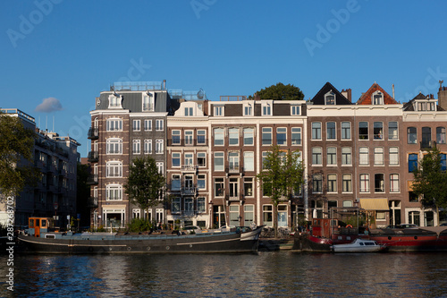 Photo  Urban city view of Amsterdam canal with mobile water living boats at sunset