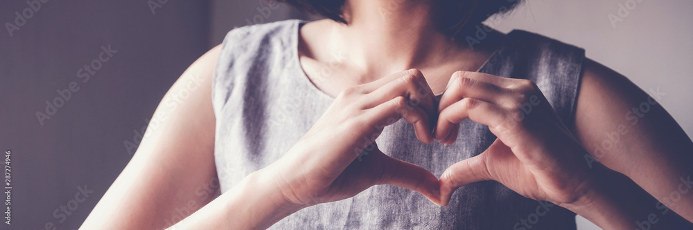 Fototapeta Happy Asian young woman making her hands in heart shape, heart health insurance, social responsibility, donation charity, world heart day,  organ donor day, International Women's Day