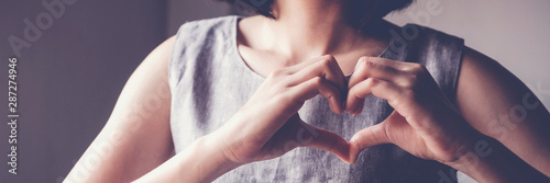 Happy Asian young woman making her hands in heart shape, heart health insurance, social responsibility, donation charity concept, world heart day, International Day of Sign Languages