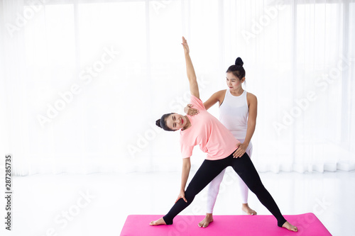 Women Doing Yoga Exercise Together One Is A Yoga Trainer One Is A Trainee Concept Of