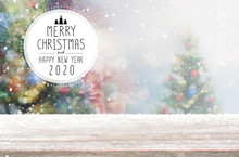 Christmas And Happy New Year 2020 On Empty Wood Table Top On Blur Bokeh Christmas Tree Background With Snowfall - Can Be Used For Display Or Montage Your Products.