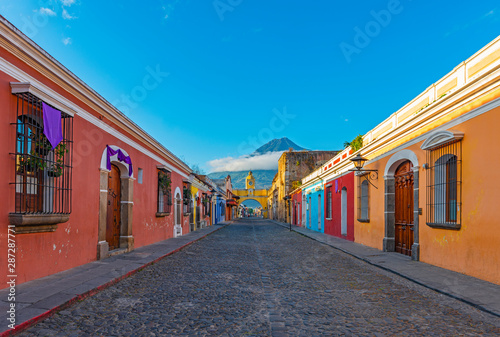 Cityscape of the colorful main street of Antigua city at sunrise with the famous yellow arch and the Agua volcano in the background, Guatemala, Central America Canvas Print
