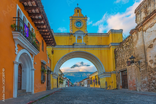 Photo The colorful yellow arch of Antigua city at sunrise with the active Agua volcano in the background, Guatemala