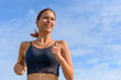 Smiling happy woman jogging outdoors in summer