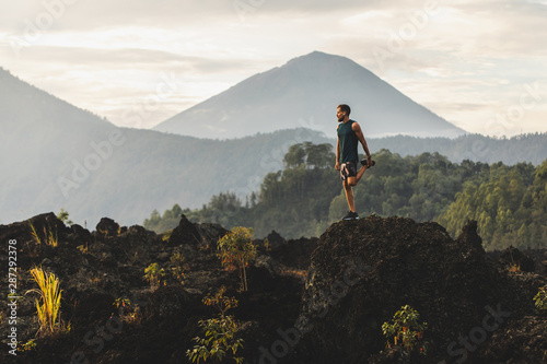 Man doing stretching and preparing for workout and running outdoors. Amazing mountain view on background. Adventure sports concept. - 287292378