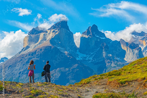 Fotografie, Tablou Two tourist, a man and a woman, looking upon a viewpoint of the Andes peaks of Cuernos del Paine, Torres del Paine national park, Puerto Natales, Patagonia, Chile