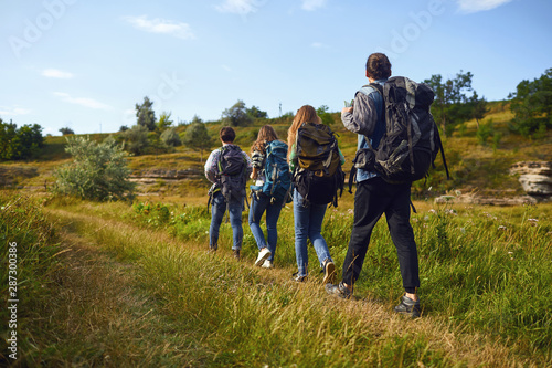 A group of tourists with backpacks is walking in nature Fotobehang