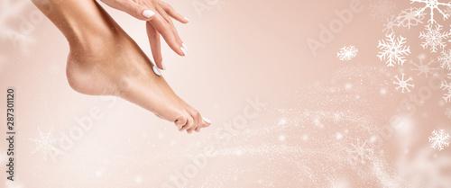 Hand applying cream on foot. Canvas Print
