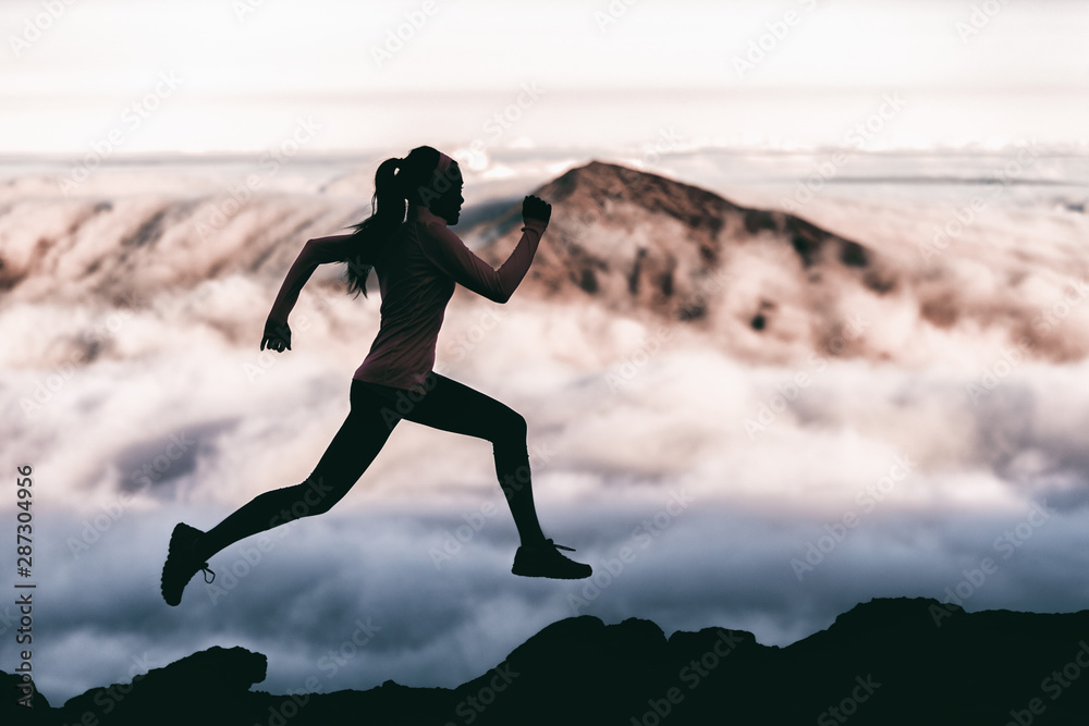 Fototapety, obrazy: Trail runner athlete silhouette running in mountain summit background clouds and peaks background. Woman training outdoors active fit lifestyle.