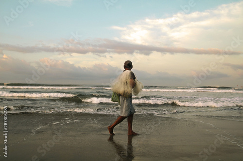Photo  Pescador caminando a la orilla del mar mirando el horizonte.