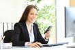 Leinwandbild Motiv Happy businesswoman posing holding smart phone at office