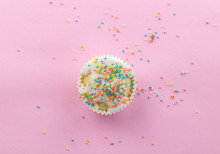 Little Frosted White Cupcake In Centre Of Pink Background Sprinkled With Multi - Coloured Sprinkles On Pink With Copy Space