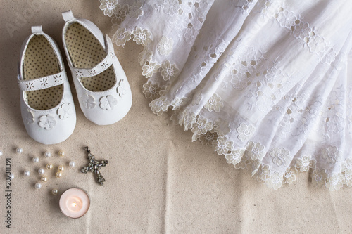 Obraz na płótnie Christening background with baptism dress, shoes, candles and crystal cross pend