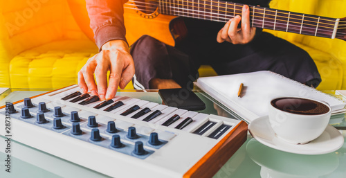 Photo male songwriter playing guitar, keyboard and writing a song in living room