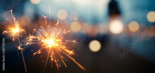 Obraz Burning sparkler with bokeh light background - fototapety do salonu