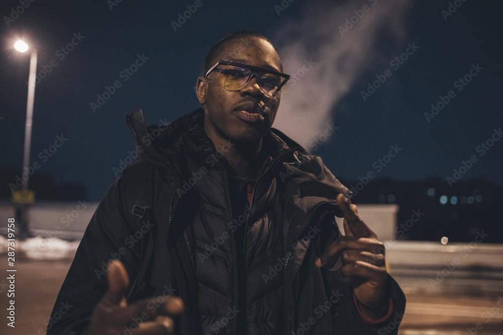 Fototapeta young african man outdoors posing looking camera