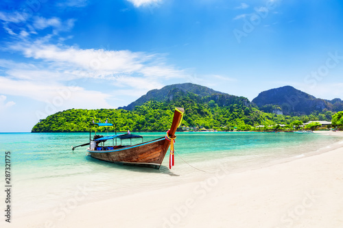 Obraz Thai traditional wooden longtail boat and beautiful sand beach. - fototapety do salonu