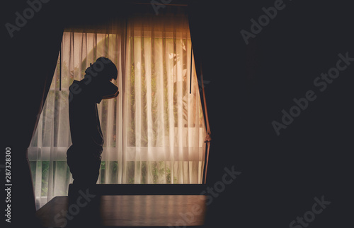 Photo Alone man silhouette standing at the window closed with curtains in darkroom