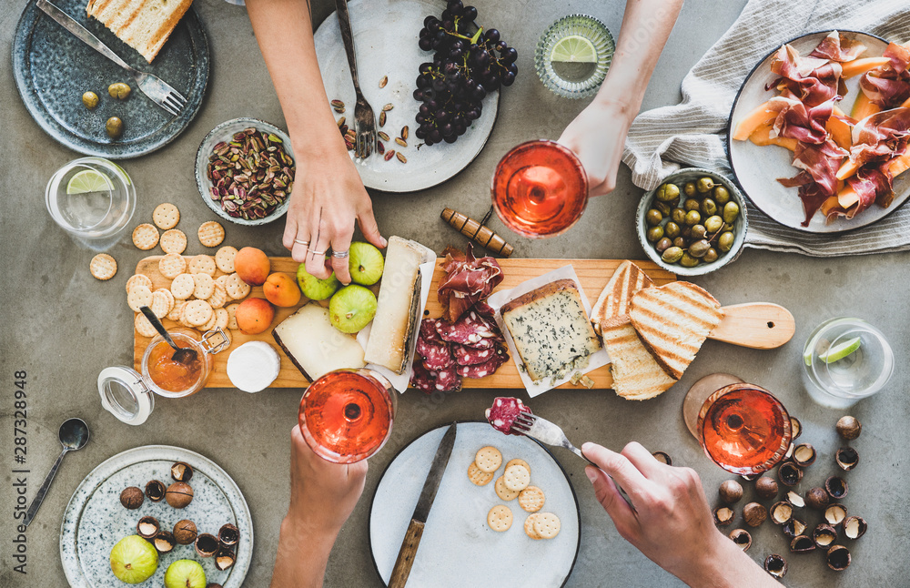 Fototapety, obrazy: Mid-summer picnic with wine and snacks. Flat-lay of charcuterie and cheese board, rose wine, nuts, olives and peoples hands with snacks and wine over concrete table background, top view
