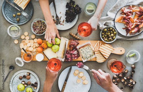 Mid-summer picnic with wine and snacks. Flat-lay of charcuterie and cheese board, rose wine, nuts, olives and peoples hands with snacks and wine over concrete table background, top view