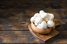 Mushrooms In A Wooden Bowl On A Wooden Table