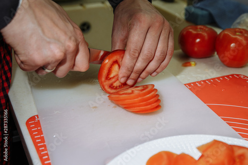 Autocollant pour porte Cuisine cutting tomatoes in the kitchen with male hands
