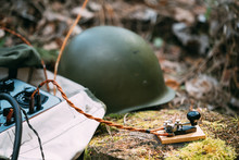 Russian Soviet Portable Radio Transceiver Used By USSR Red Army Signal Corps In World War Ii. Telegraph Key And Helmet Are On A Forest Stump