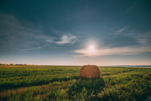 Natural Night Starry Sky Above Field Meadow With Hay Bale After Harvest. Glowing Stars And Full Moon Above Rural Landscape In August Month. Agricultural Landscape
