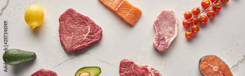 Panoramic shot of raw meat and fish near avocados, tomatoes and lemon on marble surface - 287346149