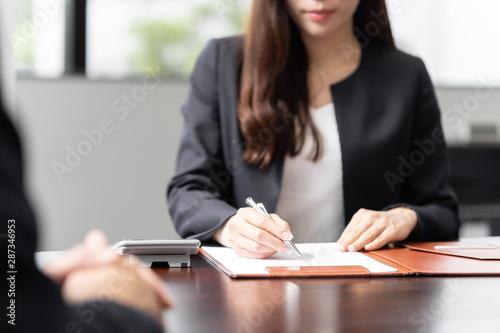 Obraz 税の相談を受け、計算をする女性税理士 - fototapety do salonu