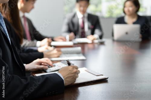 Photo 明るい会議室でミーティングをしているビジネスマン