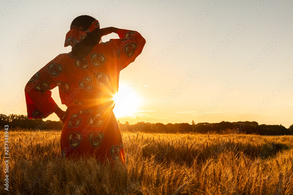 Fototapety, obrazy: African woman in traditional clothes standing in a field of crops at sunset or sunrise