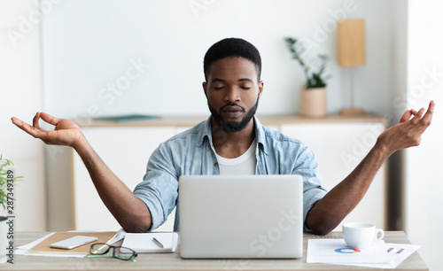 Fotomural  Relaxed african american businessman meditating at office