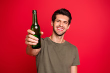 Photo Of Amazing Guy With Green Beer Ale Bottle Spending Great Time Wear Casual Grey T-shirt Isolated On Red Background
