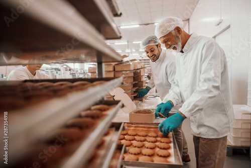 Foto op Plexiglas Bakkerij Two hardworking dedicated Caucasian employees dressed in white sterile uniforms collecting and packing cookies in boxes. Food plant interior.