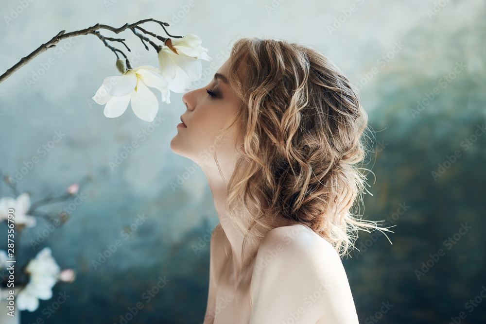 Fototapeta Perfect bride, portrait of a girl in a long white dress. Beautiful hair and clean delicate skin. Wedding hairstyle blonde woman. Girl with a white flower in her hands