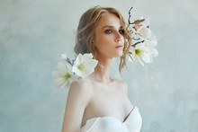 Perfect Bride With Jewels, A Portrait Of A Girl In A Long White Dress. Beautiful Hair And Clean Delicate Skin. Wedding Hairstyle Blonde Woman. Girl With A White Flower In Her Hands