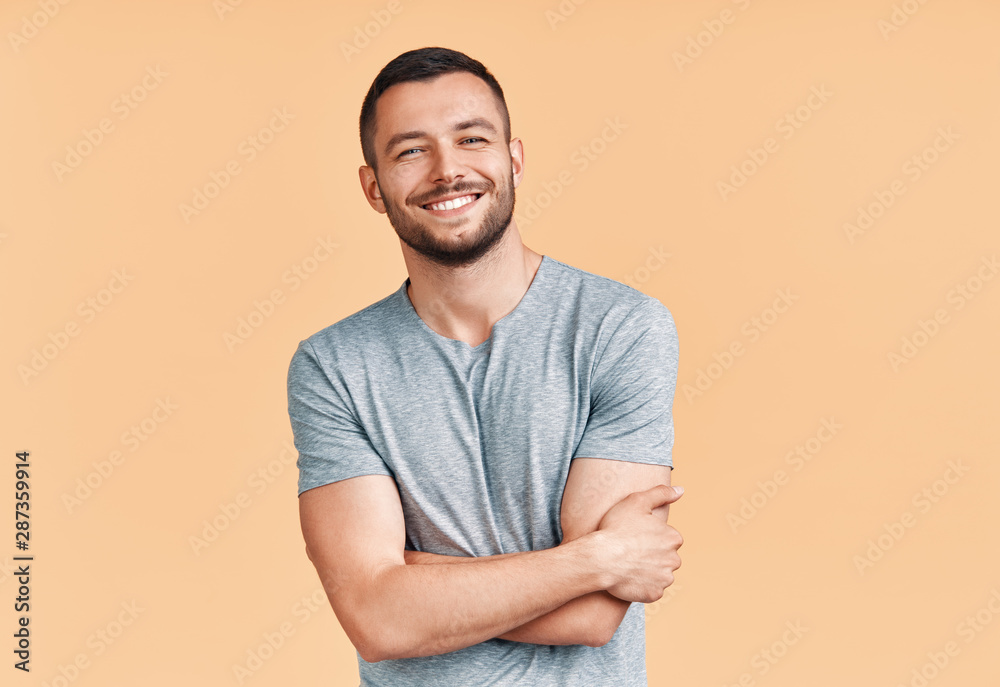 Fototapeta Happy smiling handsome man with crossed arms looking to camera over beige background