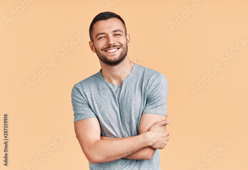 Obraz Happy smiling handsome man with crossed arms looking to camera over beige background - fototapety do salonu