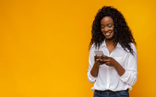 Interested African American Girl Using Smartphone On Yellow Background
