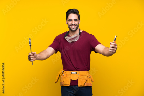 Handsome young craftsman over isolated yellow background Wallpaper Mural