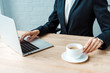 selective focus of businesswoman typing on laptop and touching cup with coffee