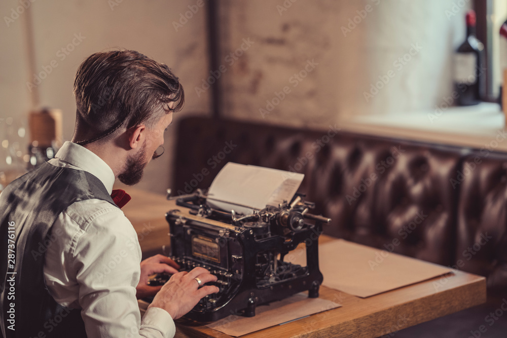 Fototapety, obrazy: Working man typing on a retro typewriter
