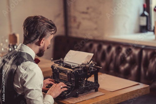 Working man typing on a retro typewriter - 287376116