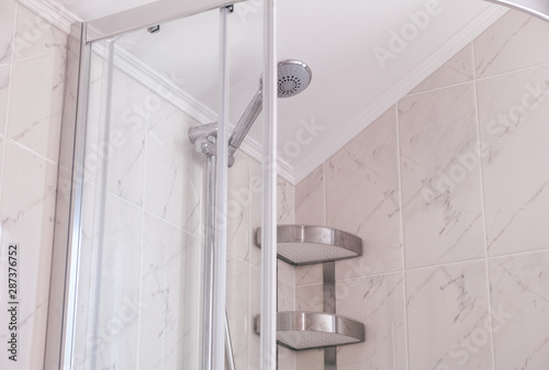 Fotografía Shower enclosure with shower head and shelf  in domestic bathroom