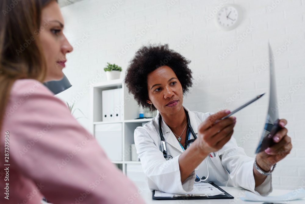Fototapeta Doctor talking with patient at desk in medical office. Health care concept, medical insurance. Womens health.