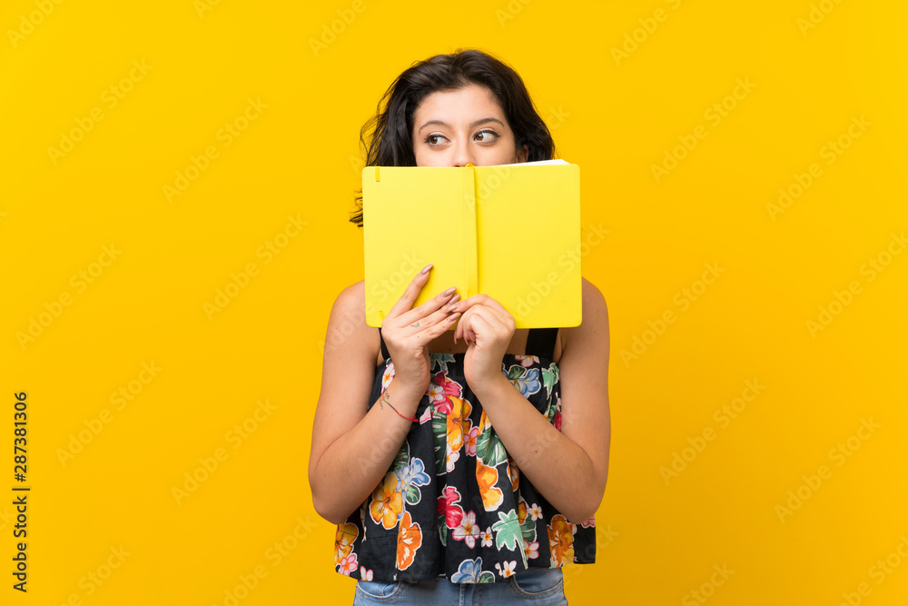 Fototapety, obrazy: Young woman over isolated yellow background holding and reading a book