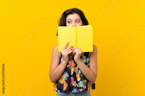 Fotografía  Young woman over isolated yellow background holding and reading a book