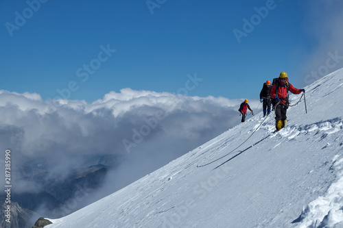 Bunch of mountaineers climbs or alpinists to the top of a snow-capped mountain Canvas Print